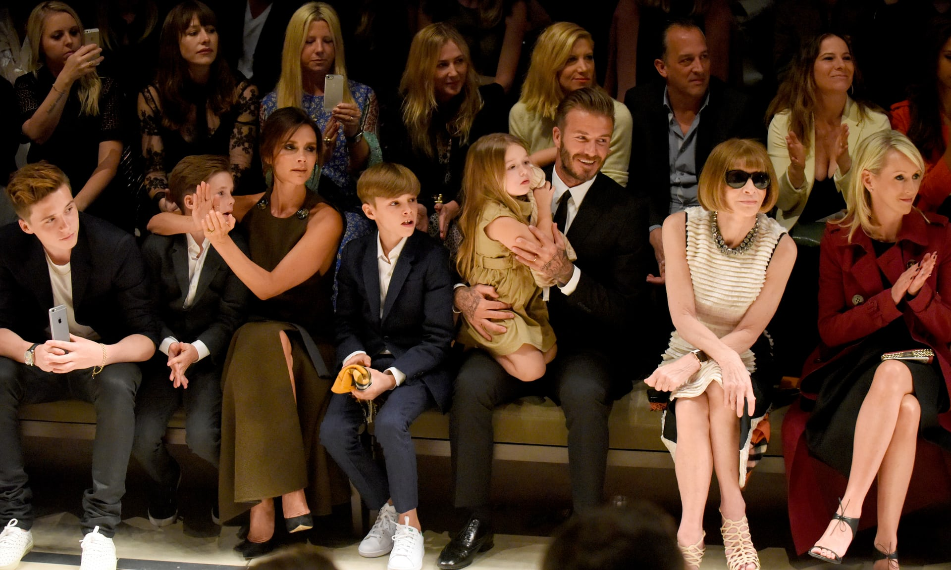 Victoria Beckham at a Burberry show in Los Angeles in April with her family. From left, Brooklyn, Cruz, Romeo, Harper, David, and the editor of Vogue, Anna Wintour..jpg