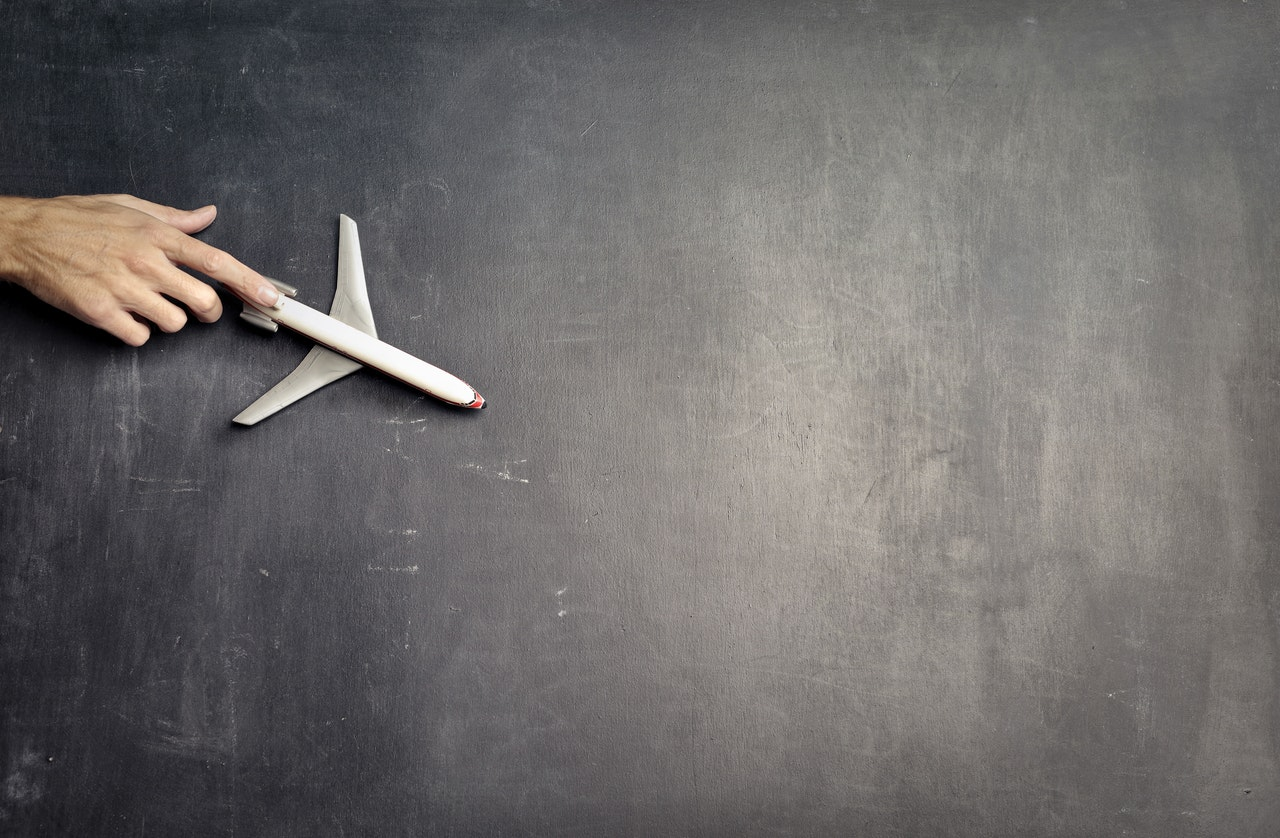 anonymous-person-with-miniature-airplane-on-chalkboard-3769120.jpg