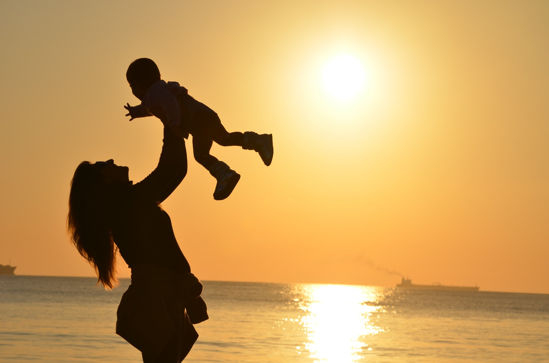 woman-carrying-baby-at-beach-during-sunset-51953.jpg